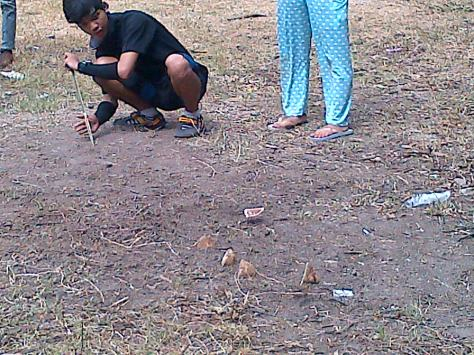 Seseorang sedang memainkan Tander-Tander (games No.6). permainan ini adalah permainan tim yang caranya melayangkan tempurung kelapa dengan kayu sehingga dapat mengenai tempurung kelapa yang telah disusun.